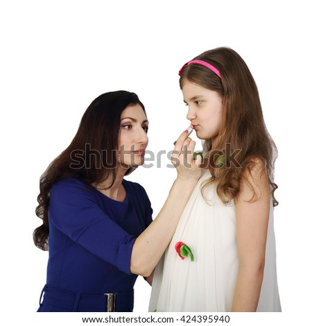 Hispanic looking woman paints girl lips with lipstick isolated on white background in square - Mother and daughter make up - stock photo