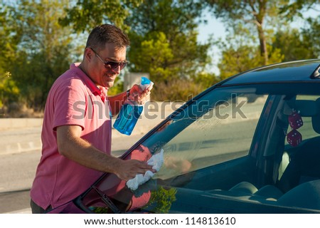 Hispanic male cleaning his car windscreen - stock photo