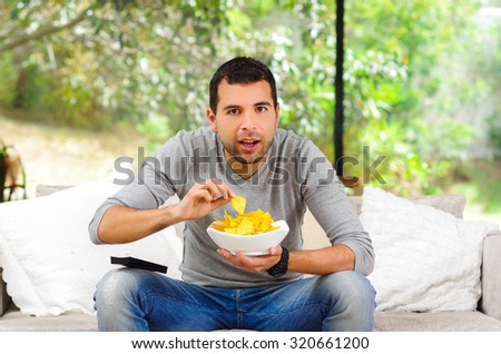 Hispanic male wearing light blue sweater plus denim jeans sitting in white sofa holding bowl of potato chips and remote control watching tv enthusiastically. - stock photo