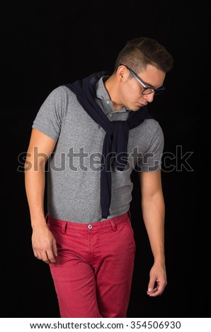 Hispanic male wearing tight shirt, sweater over shoulders, red pants and glasses portraying sophisticated hipster style, staring downwards, black background. - stock photo