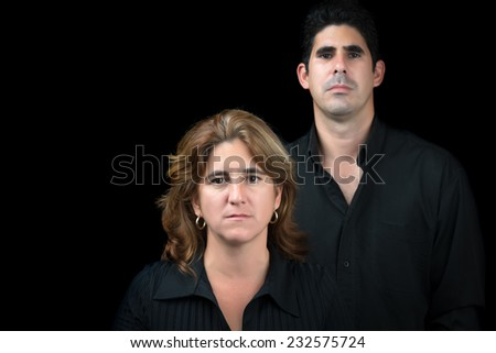 Hispanic man and woman looking at the camera isolated on a black background