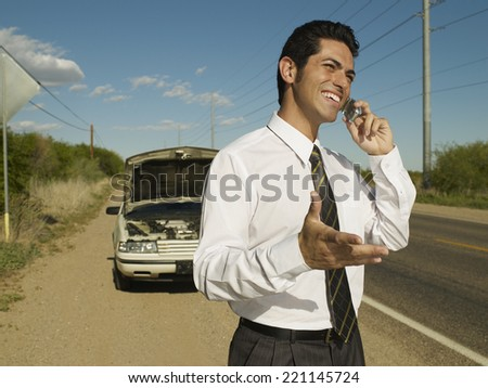 Hispanic man broken down on side of road - stock photo