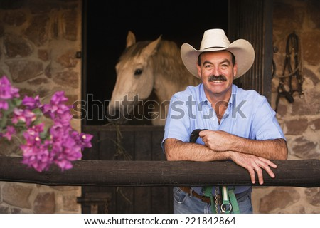 Hispanic man in front of stable - stock photo