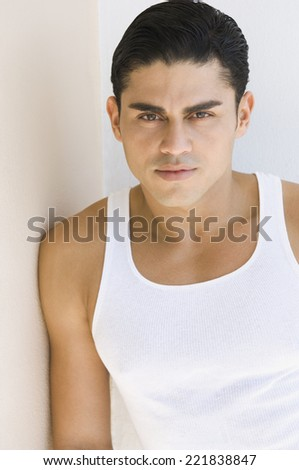 Hispanic man leaning on wall
