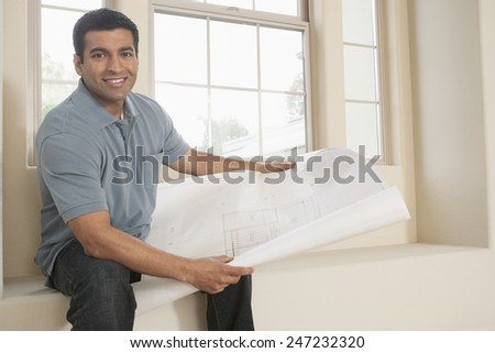 Hispanic man reading blueprints in new home