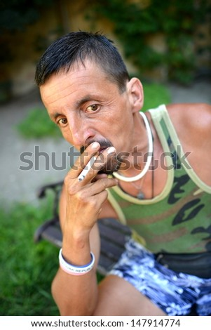 Hispanic man smoking a cigarette outdoors  - stock photo