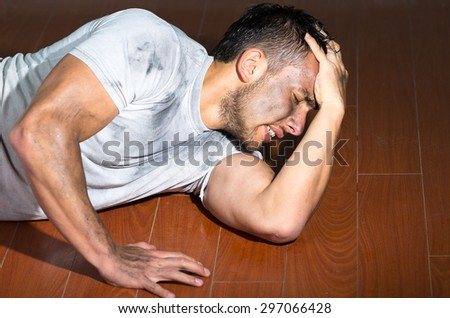 Hispanic man with dirty face and shirt lying on floor grabbing his head in frustration.