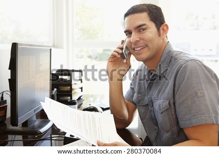 Hispanic man working in home office - stock photo