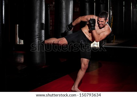 Hispanic MMA Fighter practicing some kicks with a punching bag at a gym - stock photo
