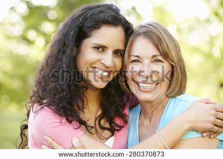 Hispanic Mother And Adult Daughter Relaxing In Park
