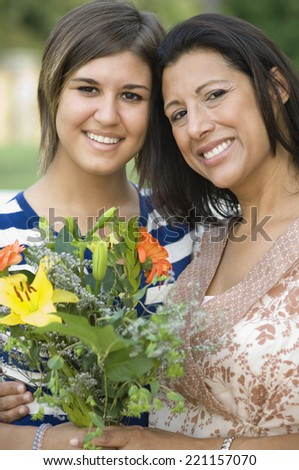 Hispanic mother and daughter holding flowers - stock photo