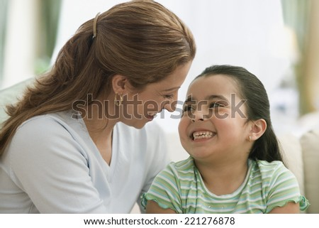 Hispanic mother and daughter smiling at each other - stock photo