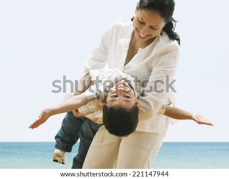 Hispanic mother and son playing at beach - stock photo