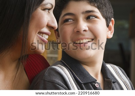 Hispanic mother and son smiling at each other - stock photo