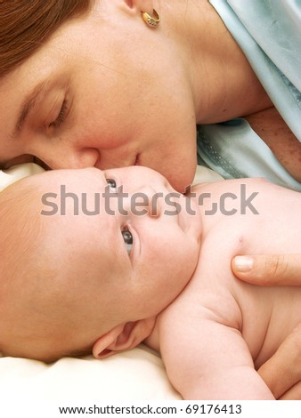 Hispanic mother enjoying her baby. Mother and new born enjoying  in bed.