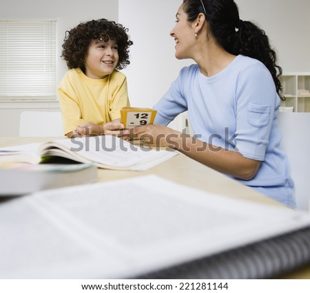 Hispanic mother helping son with homework - stock photo