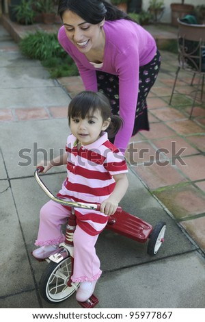 Hispanic mother helping young daughter ride tricycle - stock photo
