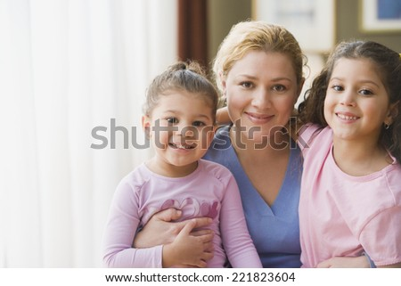 Hispanic mother hugging daughters indoors - stock photo