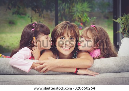 Hispanic mother in sofa with two daughters kissing her cheeks from each side, blurry garden background. - stock photo