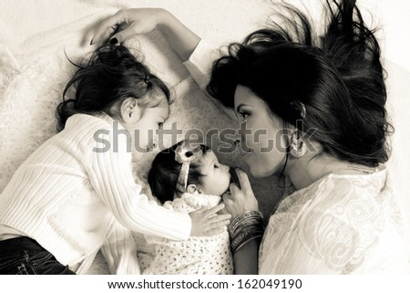 Hispanic mother laying down and looking at her two daughters - stock photo