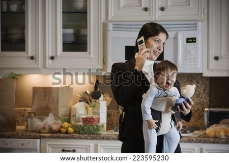 Hispanic mother on cell phone with baby in front pack - stock photo