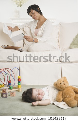 Hispanic mother reading mail while baby sleeps
