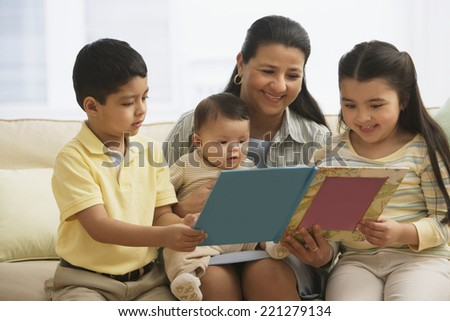 Hispanic mother reading to children - stock photo