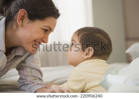 Hispanic mother smiling at baby - stock photo