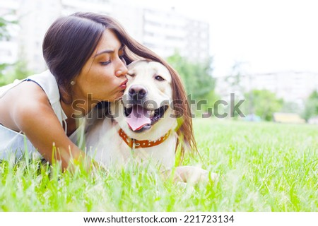 Hispanic or asian cute girl kiss white dog in summeror spring green  park on house or home and sunny sky background Empty copy space for inscription Woman with long brunette hair Simbol of protection