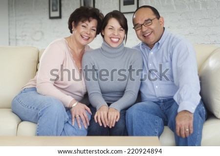 Hispanic parents and adult daughter on sofa - stock photo