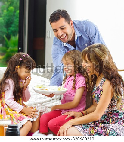 Hispanic parents with two daughters enjoying a tray of potato chips sitting in sofa while smiling and enjoying each other company.