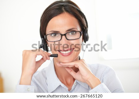 Hispanic receptionist in blue blouse conversing on her headphones while looking at you and smiling cheerfully - stock photo