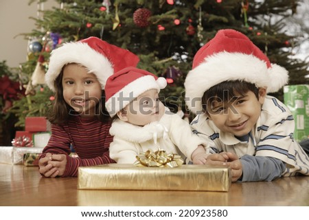 Hispanic siblings wearing Santa Claus hats - stock photo