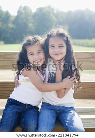 Hispanic sisters hugging on bench - stock photo