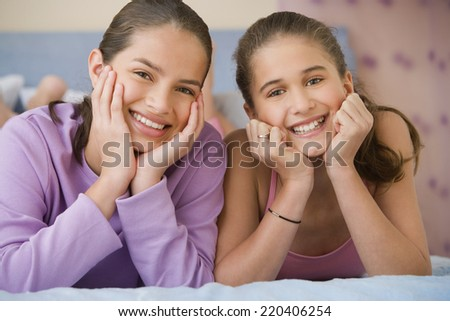 Hispanic sisters laying on bed smiling - stock photo