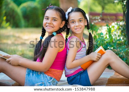 Hispanic sisters reading book in summer park  - stock photo