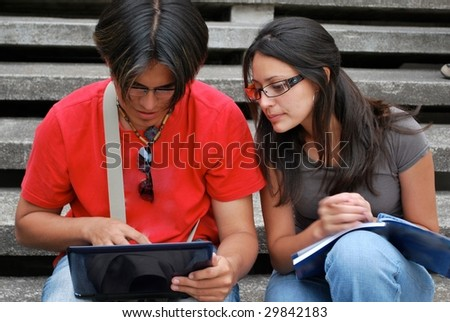 Hispanic students looking at a laptop together - stock photo