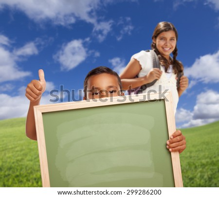 Hispanic Students with Thumbs Up in Grass Field Holding Blank Chalk Board. - stock photo