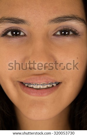 Hispanic teen girl wearing braces smiling close-up - stock photo