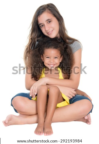Hispanic teen hugging a little african-american girl isolated on white