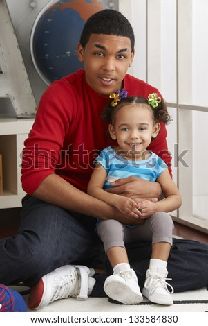 Hispanic teenage boy holding his younger sister on lap while they play at home. - stock photo