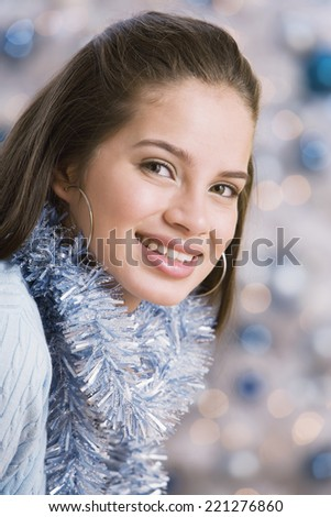 Hispanic teenaged girl wearing Christmas garland - stock photo