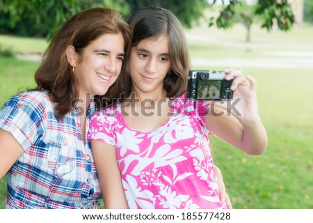 Hispanic teenager and her young mother taking a self picture at a beautiful park - stock photo