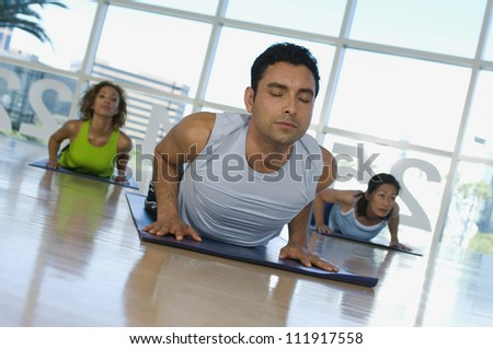 Hispanic trainer and group of people practicing yoga - stock photo