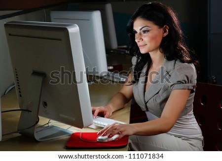 Hispanic woman at work behind a computer. - stock photo