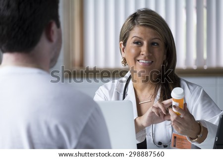 Hispanic woman doctor talking to male patient with prescription bottle.