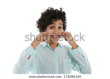 hispanic woman doing facial expression, giving herself a pinch on cheek to smile while looking at camera on white background - stock photo