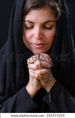 Hispanic woman dressed black and praying. Catholic woman praying with a rosary - stock photo