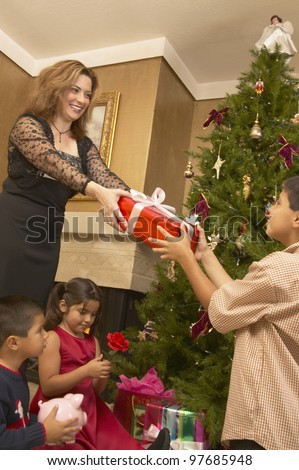 Hispanic woman giving son Christmas gift - stock photo
