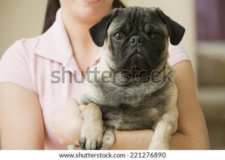 Hispanic woman holding dog